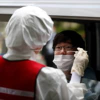 A medical worker conducts a simulation for drive-thru PCR tests for the coronavirus in Tokyo on April 22. | REUTERS