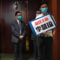 Pro-democracy lawmaker Eddie Chu holds a placard outside the chamber of the Legislative Council Complex after he was ejected minutes following a second-day legislative debate in Hong Kong on Thursday.  | AP