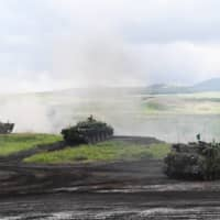 Ground Self-Defense Force vehicles take part in a live fire exercise in the East Fuji Maneuver Area in Gotemba, Shizuoka Prefecture, on Saturday. | AFP-JIJI /VIA BLOOMBERG