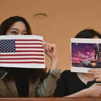 Two women hold up posters of the U.S. flag and a depiction of President Donald Trump during a rally in a shopping mall in Hong Kong on Thursday. | AFP-JIJI