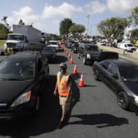 Cars line up at a food distribution center on May 15 in Compton, California. As unemployment soars amid the coronavirus pandemic, more Americans are relying on food handouts. | AP