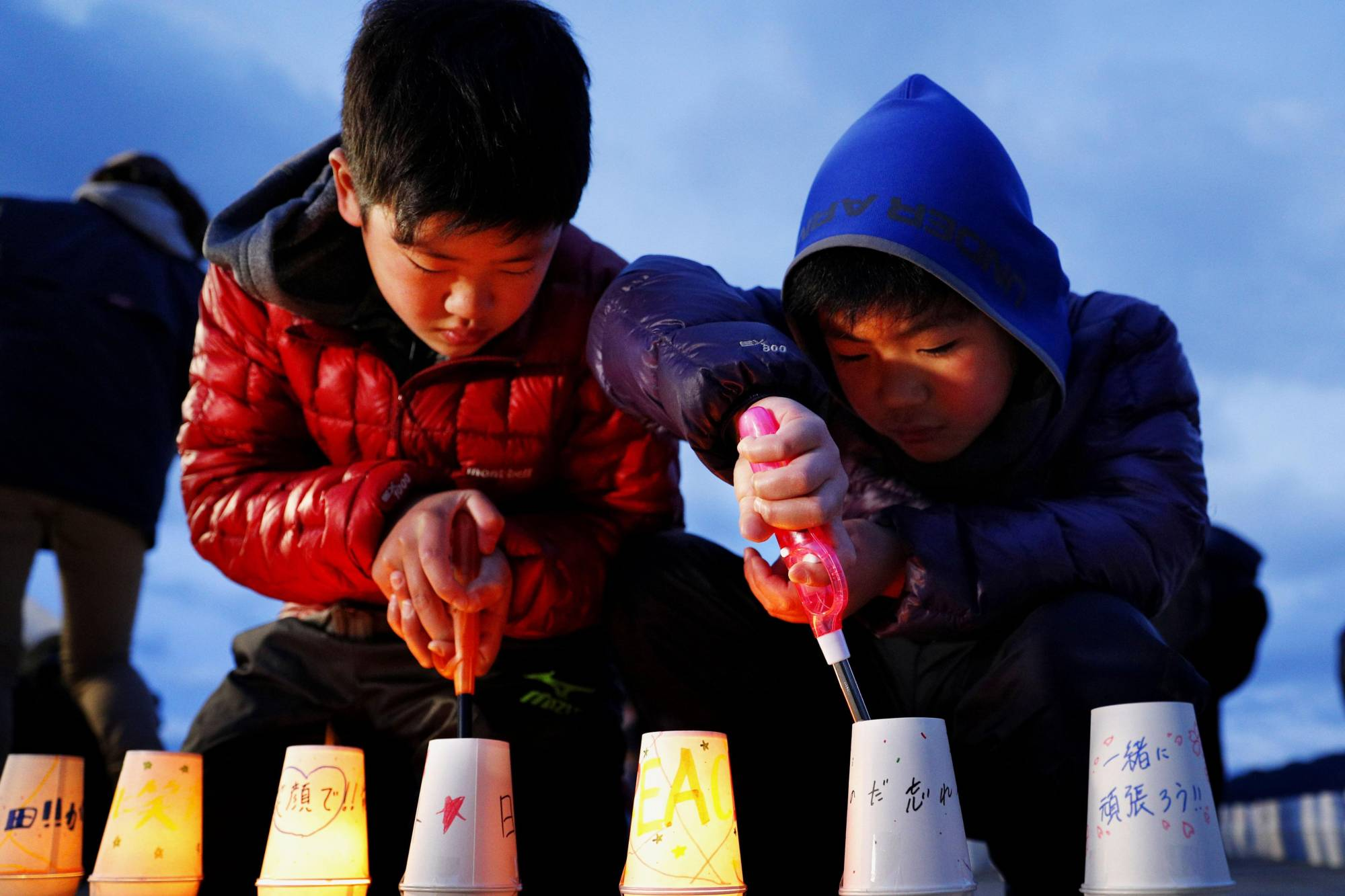 Boys light lanterns during a memorial ceremony for the March 2011 earthquake and tsunami in the town of Yamada, Iwate Prefecture, on March 11. | KYODO