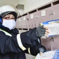A mailman delivers face masks prepared by the government in Kanazawa, Ishikawa Prefecture, earlier this month. | KYODO
