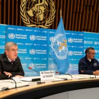 IOC President Thomas Bach (left) speaks during a news conference with World Health Organization Director General Tedros Adhanom Ghebreyesus in Geneva on May 16.  | CHRISTOPHER BLACK / WHO / HANDOUT VIA REUTERS