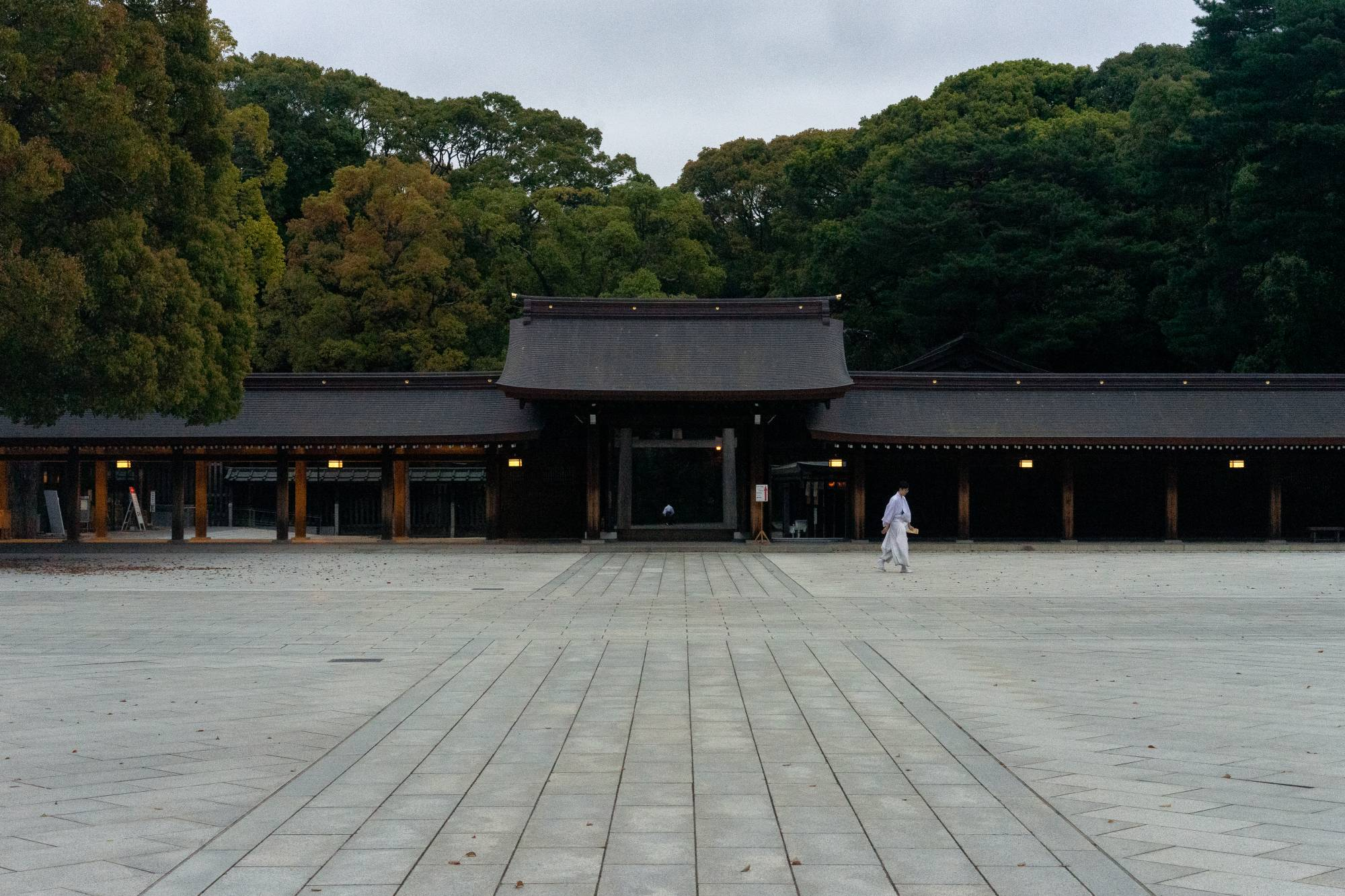 A lone monk walks through the central courtyard of Meiji Jingu, one of Tokyo's largest shrines, dedicated to the spirits of the Meiji Emperor and Empress. Located not far from Harajuku, the shrine usually receives 3 million visitors a year. Throughout the state of emergency, it was largely deserted. | OSCAR BOYD