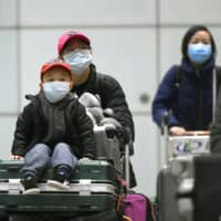 People wearing masks are seen at Beijing's international airport on March 11 amid the spread of the new coronavirus. | KYODO
