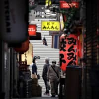 Pedestrians wearing protective masks walk through a shopping street in the Kichijoji area of Tokyo on Tuesday.  | BLOOMBERG