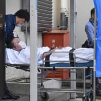 Shinji Aoba lies on a stretcher as he is brought into Fushimi Police Station in Kyoto on Wednesday after being arrested. | KYODO