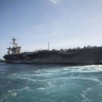 The aircraft carrier USS Theodore Roosevelt departs Naval Base Guam on May 21 on a training mission after being sidelined with a coronavirus outbreak for nearly two months. | U.S. MARINE CORPS /VIA AP