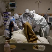 Medical workers wearing personal protective equipment take care of a patient suffering from the coronavirus in New Delhi on Thursday.  | REUTERS