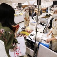 A sales clerk wearing a face mask and a face shield serves a customer in a food section of a partially reopened Matsuya department store outlet in Tokyo's Ginza district on Monday. | KYODO