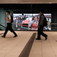 Pedestrians walk past a screen inside a showroom at Nissan Motor Co.'s headquarters in Yokohama on Tuesday. | BLOOMBERG