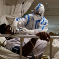 A medical worker takes care of a patient suffering from the coronavirus at the the Max Smart Super Speciality Hospital in New Delhi on Thursday.  | REUTERS