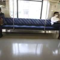 Train passengers practice social distancing. Tokyo reported 22 new infections Friday. | AP