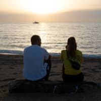 A couple relaxes on a beach in Barcelona. Lingering health concerns and uncertainty about which borders will open mean many people will stick close to home this summer. | AFP-JIJI