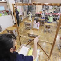 With a plastic shield between her and the class, a teacher addresses her pupils at an elementary school in Funabashi, Chiba Prefecture, earlier this month. | KYODO