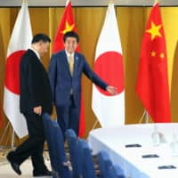 Prime Minister Shinzo Abe escorts Chinese leader Xi Jinping during the Group of 20 summit meeting in Osaka last year. | KYODO