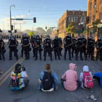 People sit on the street in front of a row of police officers during a rally in Minneapolis on Friday.  | AFP-JIJI