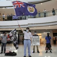 Protesters wave a Hong Kong colonial flag in a shopping mall during a protest against China's national security legislation for the city on Friday. The British government says it will grant nearly 3 million Hong Kong residents greater visa rights if China doesn't scrap a planned new security law for the semiautonomous territory.  | AP
