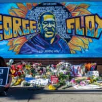 Flowers, signs and balloons are left near a makeshift memorial for George Floyd on May 29 in Minneapolis. The memorial was placed near the spot where he died while in the custody of the Minneapolis police on May 25.  | AFP-JIJI