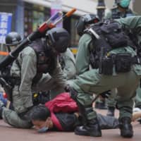 Riot police detain a protester during a demonstration against Beijing's national security legislation in the Causeway Bay area of Hong Kong on May 24. | AP