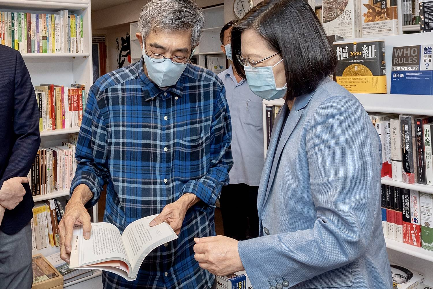 Taiwan's President Tsai Ing-wen looks at a book while visiting Lam Wing-kee, a bookseller from Hong Kong who in 2015 was detained in China for allegedly bringing banned books into the mainland.  | TAIWAN PRESIDENTIAL OFFICE / VIA AFP-JIJI