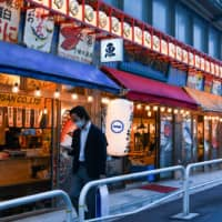A pedestrian wearing a protective mask walks past a traditional Japanese pub in the Yurakucho district of Tokyo on Friday.  | BLOOMBERG
