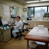 Toshihiko Yamazaki, a doctor who is also the director of the National Federation of Health Care Organizations, works at his urology clinic in Urawa, Saitama Prefecture, on May 22. | REUTERS