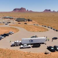 People line up in their vehicles to collect water and supplies from a distribution point as COVID-19 spreads through Navajo Nation, in Monument Valley at the Utah and Arizona border, in May.  | AFP-JIJI