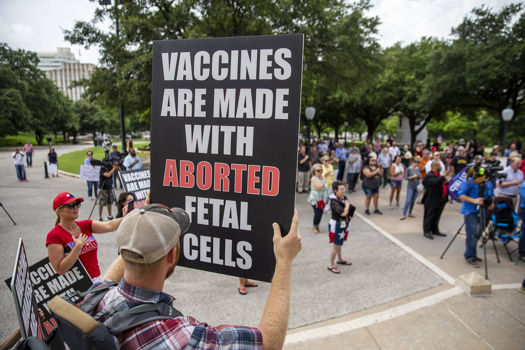 The Texas Freedom Rally protesters demonstrate on the south steps of the state Capitol on May 23 in Austin, Texas. As more sectors of the Texas economy reopened from the freeze of the coronavirus pandemic, a few dozen anti-government demonstrators rallied Saturday to demand that all limitations be lifted.    AUSTIN AMERICAN-STATESMAN / VIA AP