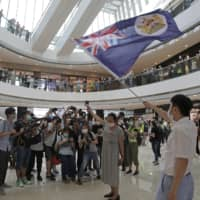Protesters in Hong Kong hold a British National (Overseas) passport and Hong Kong colonial flag in a shopping mall during a protest against China's national security legislation for the city on Friday.  | AP