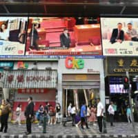 Chinese President Xi Jinping is shown on a large video screen in Hong Kong on Thursday during a live broadcast of the National People's Congress in Beijing. | AFP-JIJI