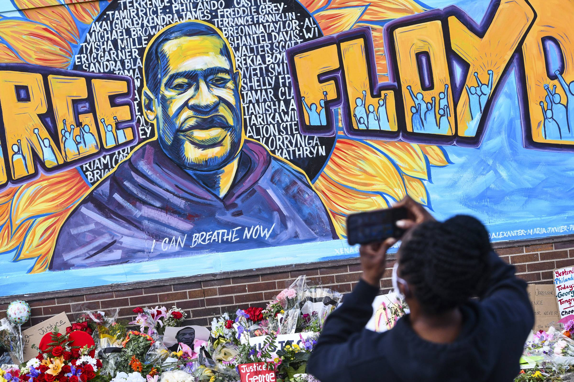 A person takes photographs of a mural in memory of George Floyd in Minneapolis on Friday.  | ST. CLOUD TIMES / VIA AP