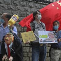 Pro-China supporters hold an effigy of U.S. President Donald Trump and a Chinese national flag outside the U.S. Consulate during a protest in Hong Kong on Saturday.  | AP