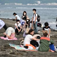 People wear face masks as they gather on a beach in Kamakura, Kanagawa Prefecture, on Saturday. | AFP-JIJI