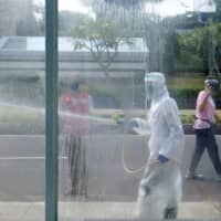 Red cross staff spray disinfectant to prevent the spread of COVID-19 in Jakarta, Indonesia, on Sunday. | REUTERS