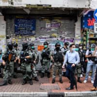 Pedestrians walk past a group of riot police standing guard in a front of a shop in the Causeway Bay district of Hong Kong on Wednesday. | AFP-JIJI