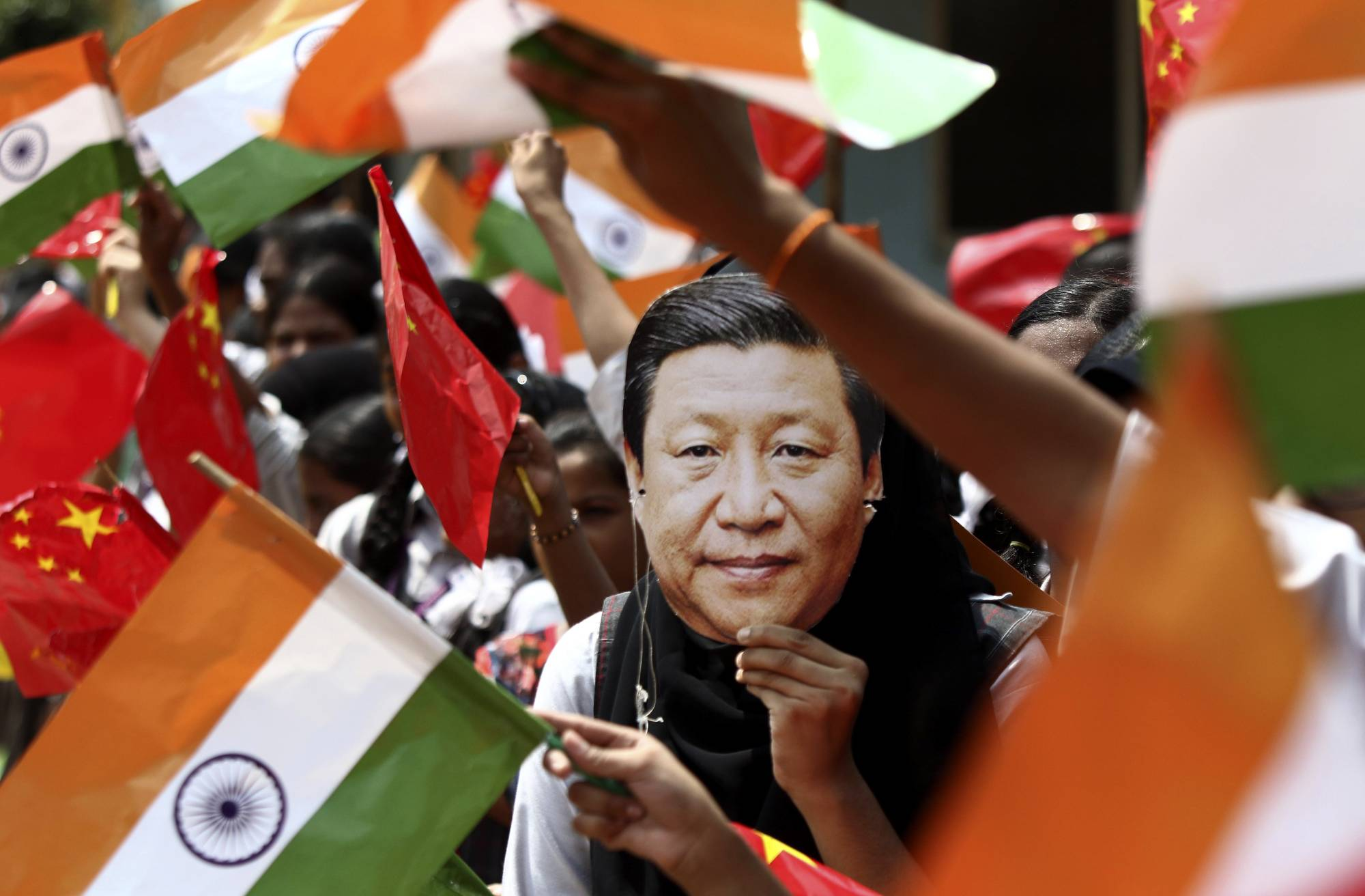 An Indian schoolgirl wears a face mask of Chinese President Xi Jinping to welcome him on the eve of his visit in Chennai, India, last October. Tensions along the China-India border high in the Himalayas have flared again in recent weeks. | AP