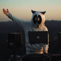 CLiONE, a hikikomori DJ based in Tokyo, dons a custom mascot head to keep his appearance a mystery during music videos and live streams on YouTube. | COURTESY OF CLIONE AND JINOFILMS / VIA KYODO