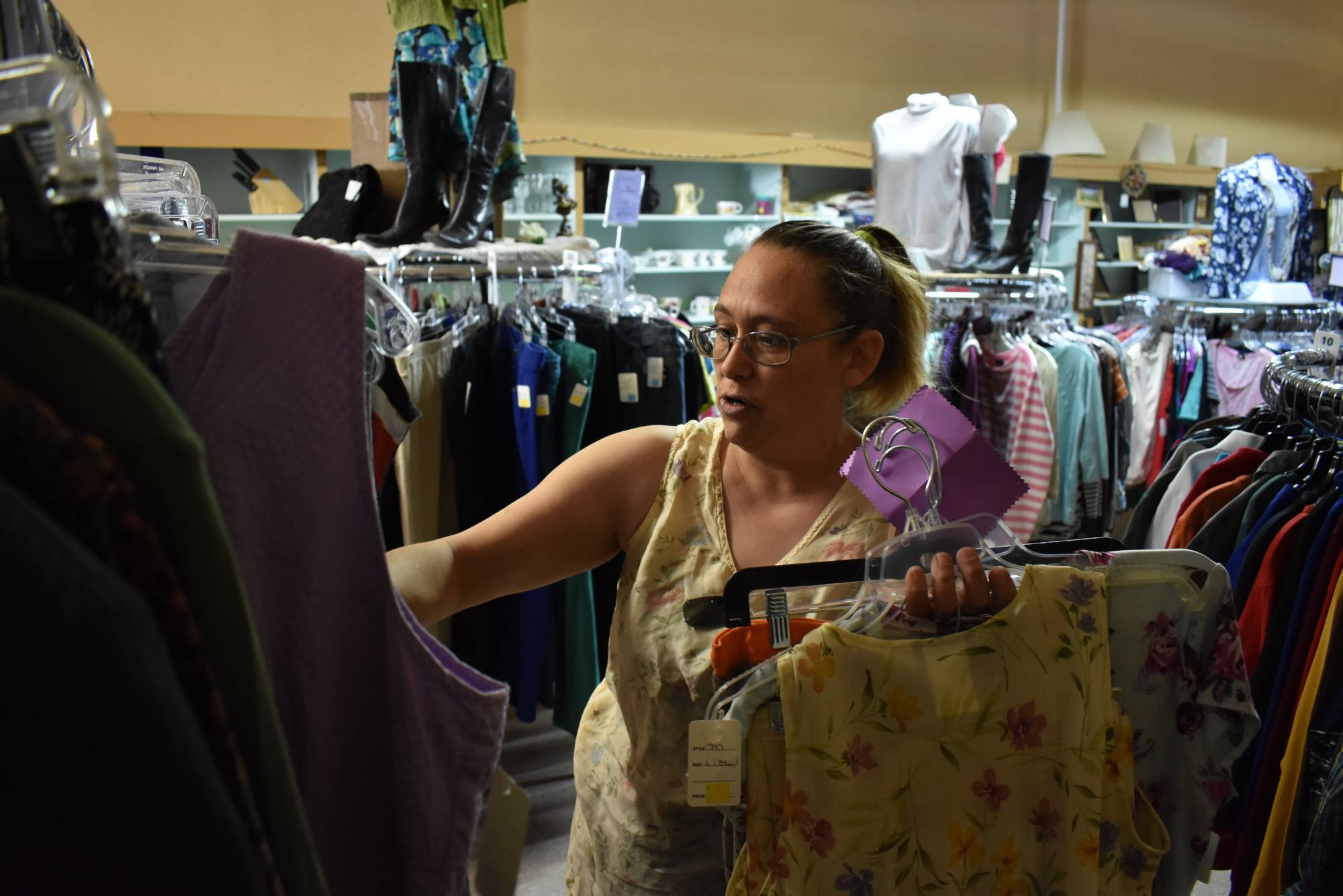 Shannon Thompson looks through clothing items at the Northern Treasure thrift store last Monday in Roundup, Montana. | AP