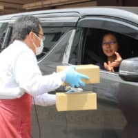 A driver receives a box of frozen meat products at a drive-thru meat store in Toyohashi, Aichi Prefecture. | CHUNICHI SHIMBUN