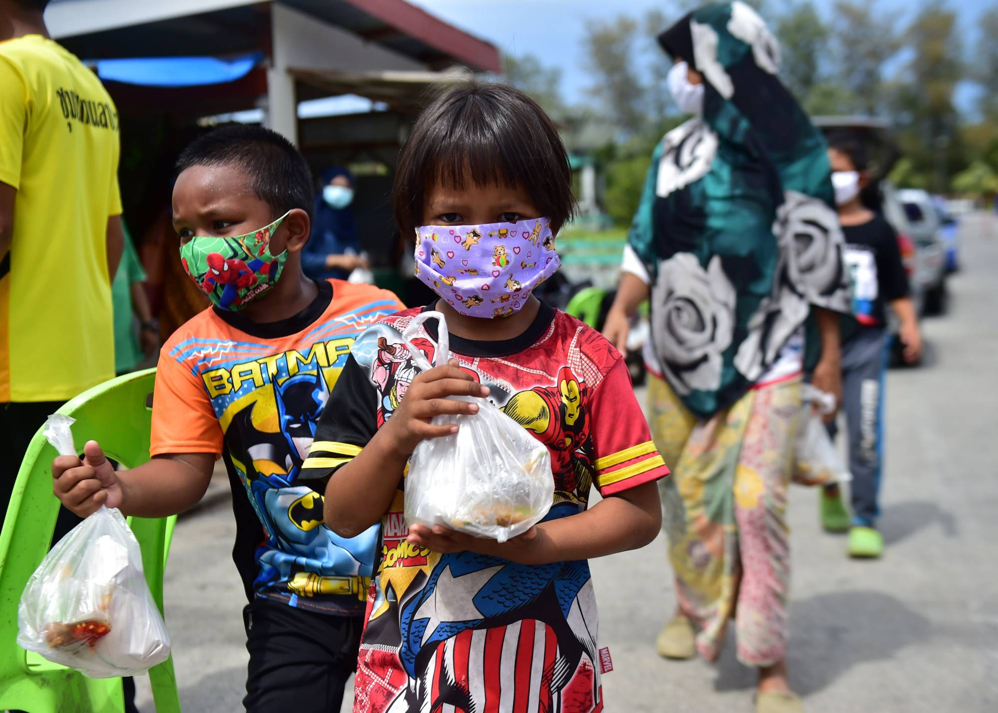 Children carry food donations in Thailand's southern province of Narathiwat on April 23. The Distance Learning Television program that was developed for learners in remote rural areas is now being extended nationwide with new courses being recorded to broaden the curriculum. | AFP-JIJI