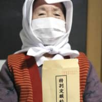 A woman in the village of Nishimeya, Aomori Prefecture, shows an envelope containing a ¥100,000 cash handout she received on Thursday. | KYODO