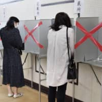 Voters practice social distancing at a polling station in the city of Shizuoka on April 26. | KYODO