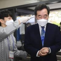 An election official takes the temperature of Lee Nak-yon, South Korea's former prime minister and a candidate from the ruling Democratic Party of Korea, at a polling station during parliamentary elections in Seoul on April 15. | BLOOMBERG