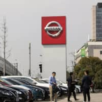 The Nissan Motor Co. logo is displayed at a car dealership in Shanghai in March 2019. | BLOOMBERG