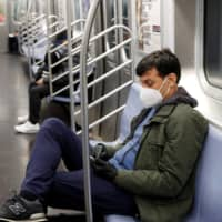A commuter wears a mask while riding the subway in New York on Thursday | REUTERS