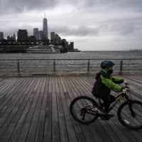 A boy wears a face mask as he bikes in New York on Thursday. | AP