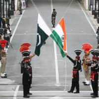 Pakistani Rangers (wearing black uniforms) and Indian Border Security Force officers lower their national flags during a parade near Lahore, Pakistan, in August 2019.   REUTERS