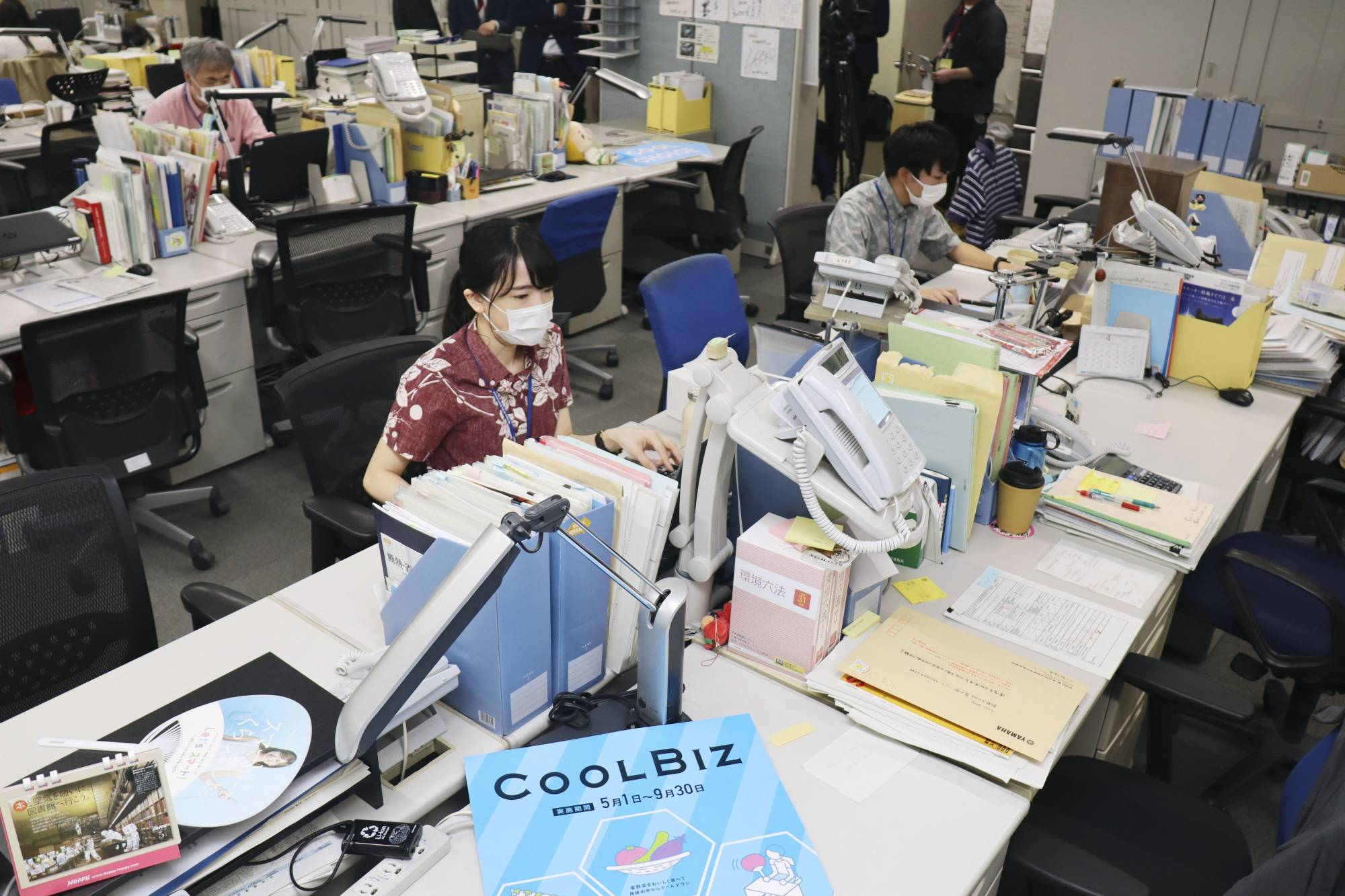 Environment Ministry officials, dressed more casually than usual, work in Tokyo on Friday, at the start of the 16th annual 'Cool Biz' campaign that is part of efforts to reduce energy use nationwide. | KYODO